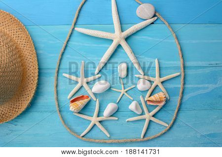 beach accessories on wooden board. Composition from sea stars, rope and shells.