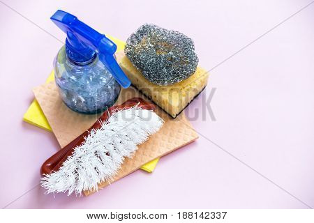 Sponges and household brushes for cleaning the house on a pink background