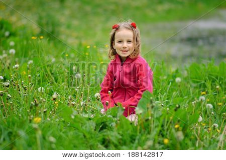 A girl is sitting in the grass on the bank of a lake, a river. The child looks seriously at the lens. Concentrated look, curly hair, fleece jacket.. Children Protection Day.
