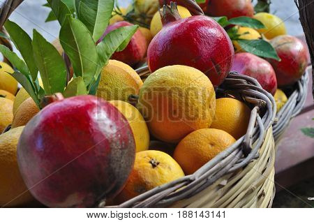 Pomegranates and fresh oranges in a basket