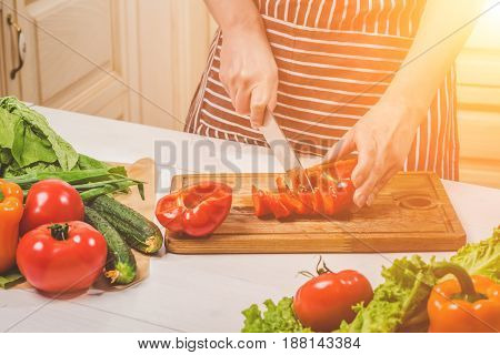 Young woman cooking in the kitchen at home. Healthy food. Diet. Dieting concept. Healthy lifestyle. Cooking at home. Prepare food. A woman cuts a pepper and vegetables with a knife.