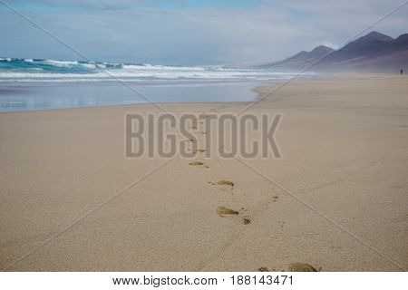 Footprints in sand on beautiful Cofete beach, Fuerteventura, Canary Islands, Spain.