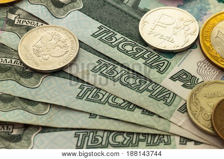 A handful of Russian coins of different denominations against the background of one thousand bills