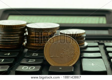 coins are in stacks on the keyboard of the calculator
