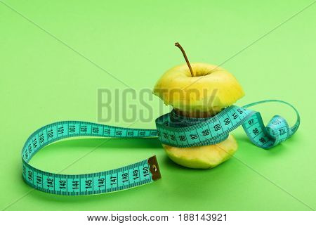 Diet and fitness concept holding green apple on light green background tied around with measure tape