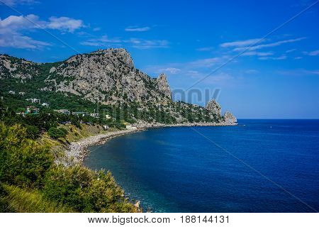Rock covered with green vegetation hanging over the calm blue sea in a bright summer day