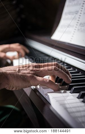 Male hand playing the keys of piano