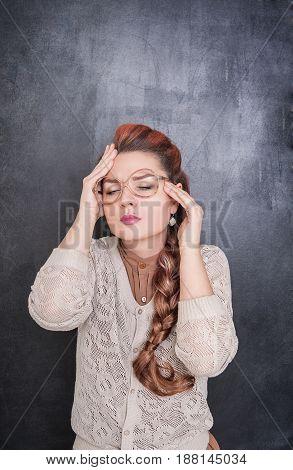 Beautiful Teacher With Headache On The Chalkboard Background