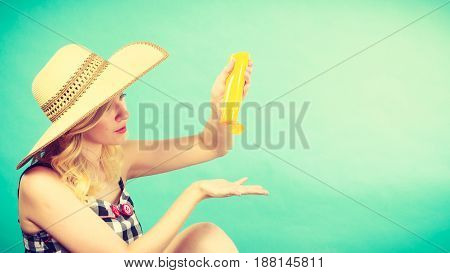 Sunburns safe sunbatching tannig during summer concept. Woman wearing sun hat applying sunscreen on hand. Studio shot on blue background