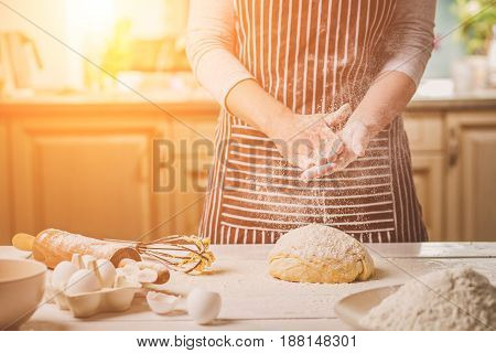 Woman slaps her hands above dough closeup. Baker finishing his baking, shakes flour from his hands, free space for text. Homemade bakery, cooking process concept