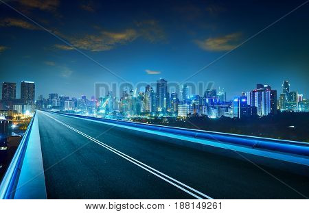 Empty asphalt flyover with city skyline night scene .