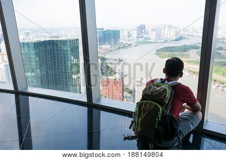 A man sitting to see a view ho chi min city at Vietnam