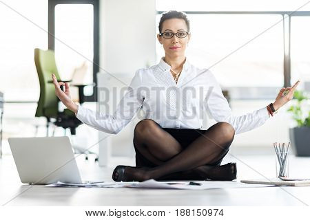 Portrait of woman expressing calmness while making yoga on working place. Office concept