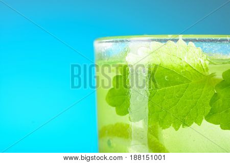 A Glass Of Mojito With Ice, Lime Wedges And Mint