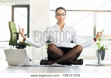 I am cool. Serene female trying to have balance between job and resting in office. Yoga concept