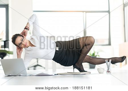 Happy girl doing exercises during working day. She kneading muscles on table in apartment. Healthy concept
