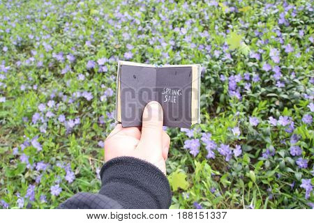Guy holding a book with an inscription on the background of a spring field with blue flowers