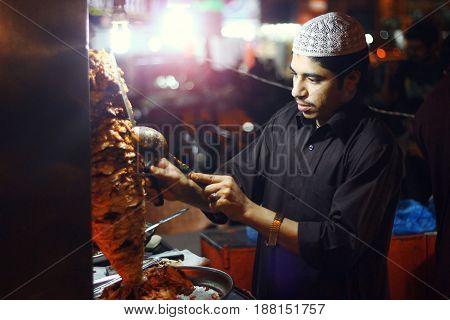 Young guy smaking shawarma at Bahadurabad Karachi Pakistan 13/03/2013
