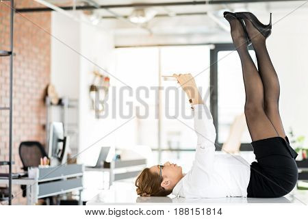 I need more comfort. Side view female expressing relaxation. Secretary watching at tablet while lying on table in wide cozy office