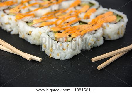 sushi pinwheels and spicy drizzle sauce on black slate with chopsticks
