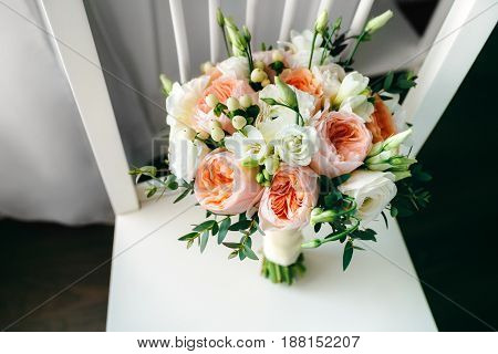 Wedding bouquet on the white wooden chair. close-up. Indoors.
