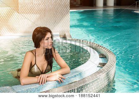 Portrait of beautiful woman in spa jacuzzi. Body care. Woman with perfect body in bikini