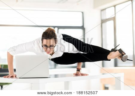 I need relaxation during my job. Female expressing happiness while looking at screen of notebook computer. She locating on desk in athletic position. Rest concept