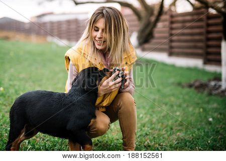 Happy Woman Enjoying Time With Cheerful Rottweiler Puppy