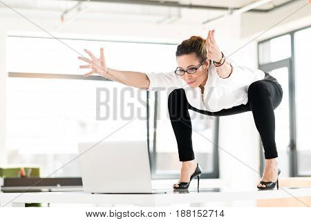Low angle smiling secretary making sport exercise in modern office while watching at laptop. Copy space