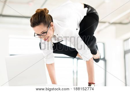 Low angle woman expressing happiness while standing on hands. She making gymnastics during at job
