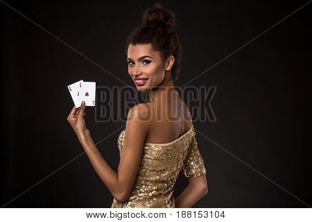 Woman winning - Young woman in a classy gold dress holding two aces, a poker of aces card combination. Studio shot on black background. A young woman stands with her back