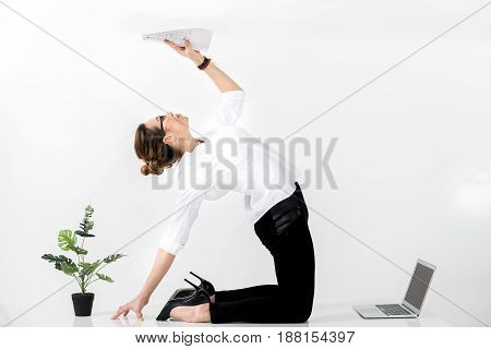 It is hard to sit all day during work. Side view calm woman looking at document while working with laptop. Copy space