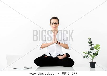 Portrait of cheerful woman making yoga exercise during work. She having balance between inner and external world. Rest concept