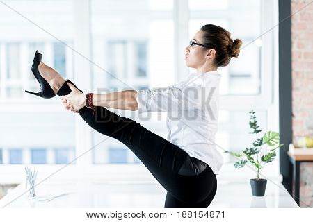 Side view serene woman making gymnastics during job in modern apartment