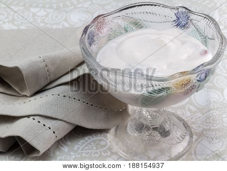 Natural greek yoghurt with berries mixed in lovely glass bowel with napkin - Food background with space for text