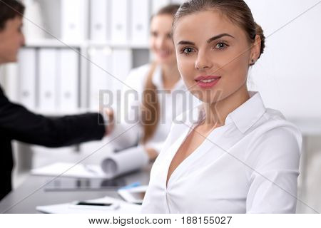 Group of business people at meeting on the background of office. Focus on a beautiful brunette.