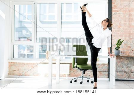 Side view cheerful girl standing in vertical twine. She leaning on table in bright room
