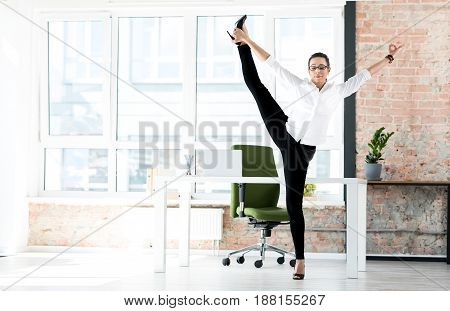 Serene female secretary stretching legs at job. She locating in wide apartment