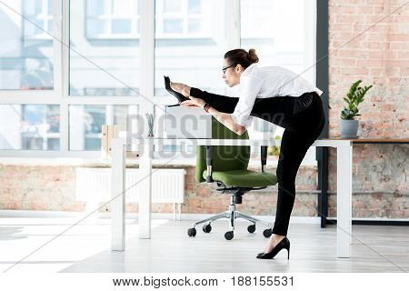 Serene lady doing gymnastics while standing near table in wide apartment