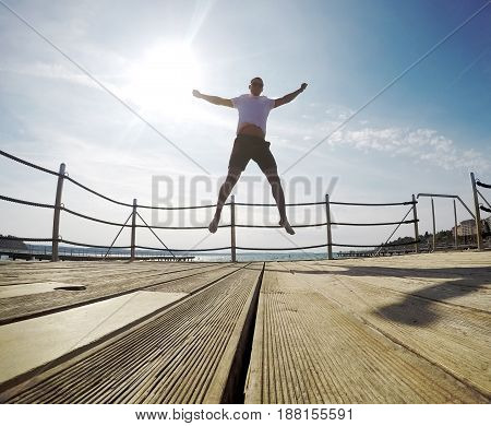 young man jumping happy on pier sunny summer day