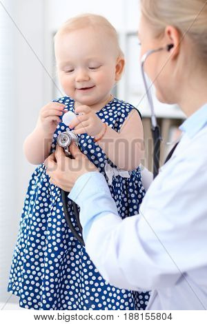 Pediatrician is taking care of baby in hospital. Little girl is being examined by doctor with stethoscope. Health care, insurance and help concept.