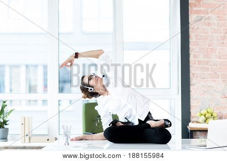 Calm female doing exercises while working in apartment. She speaking by headphones. She siting on table