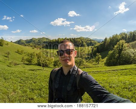 young man makin selfie on green valley landscape background