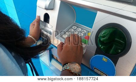 Finance, money, bank and people concept - close up of hands with wallet withdrawing cash at ATM machine.