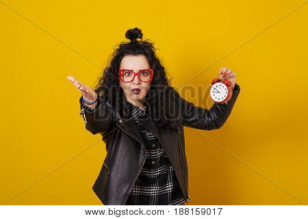 Beautiful surprised young woman with alarm clock standing in front of a yellow background.