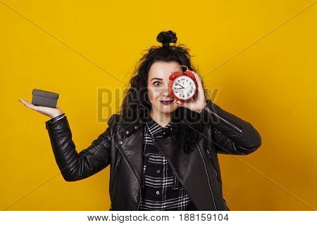 Young stylish woman holding a little gift box in one hand and alarm clock before her face standing in front of the yellow background.