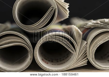 Rolled up newspapers close up background / texture