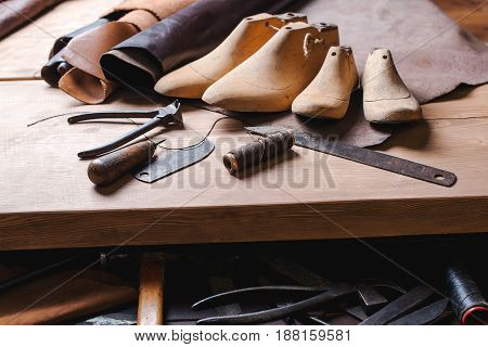 Leather in rolls cobbler tools and shoe lasts in the workshop. Leather craft tools.