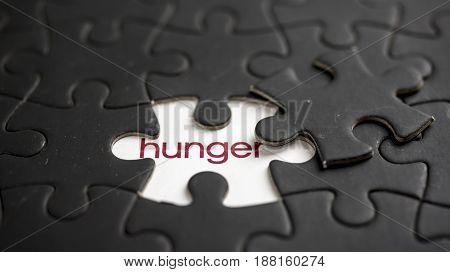 Word hunger under black jigsaw puzzle piece