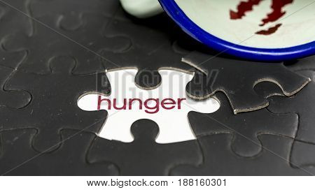 Word hunger under jigsaw puzzle piece with bloody cup on the side